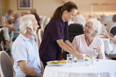 caregiver serving meal to senior couple
