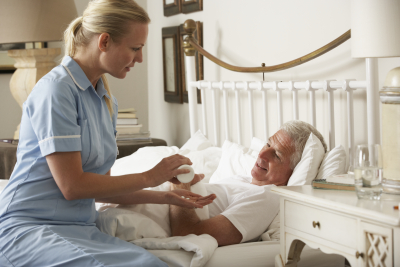 a caregiver giving the medicine to a sick senior man