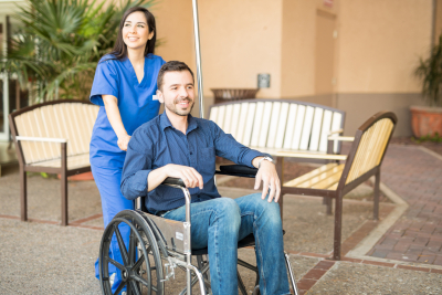 male patient being pushing on a wheelchair by a nurse