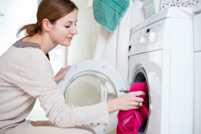 a woman putting out cloths inside washing machine